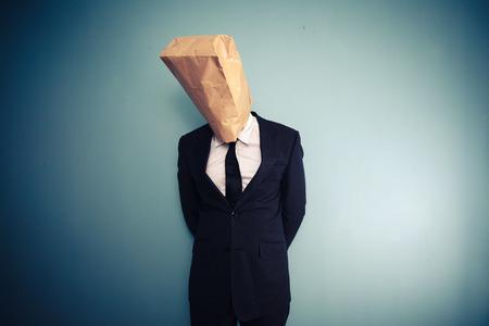 avergonzado: Hombre de negocios triste y avergonzado con la bolsa de papel sobre su cabeza