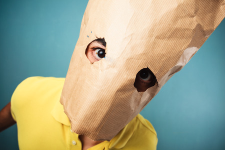 Young man with a paper bag over his head is looking at the camera through his eye holes