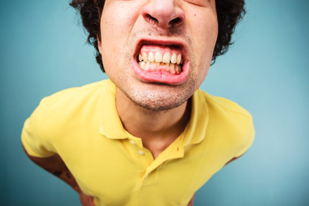 Young man is grinding his teeth and looking angry photo