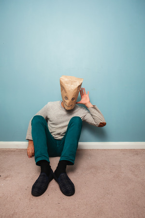 Man with a bag over his head is sitting on the floor and listening photo