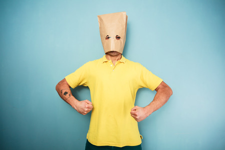 flexed: Young man with a bag over his head standing with his arms flexed Stock Photo