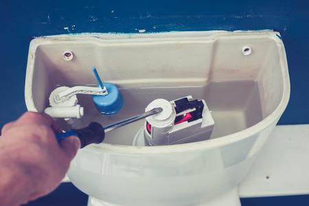 Hand wird zur Festsetzung einer Toilette Zisterne zu Hause Standard-Bild - 25769742