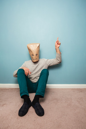 Man with a bag over his head is sitting on the floor and pointing photo