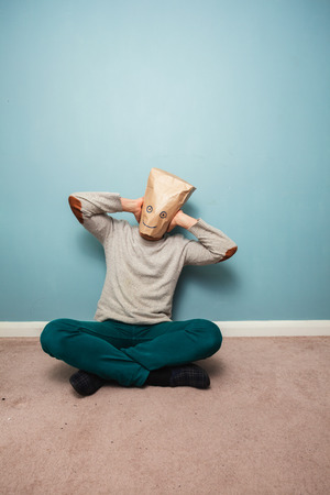 Man with a bag over his head is sitting on the floor and covering his ears photo