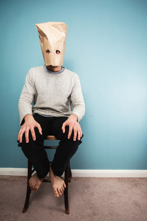 A Man with a paper bag over his head is sitting on a chair against a blue wall photo