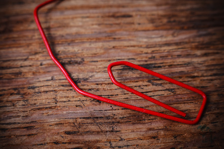 useless: Crumbled up an useless red paperclip