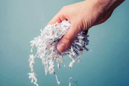 shred: Hand is holding a bunch of shredded paper Stock Photo