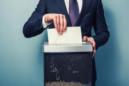 Un hombre de negocios es la trituración de documentos importantes Foto de archivo