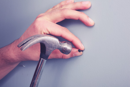 Close up on a hand hammering a nail on a wall photo