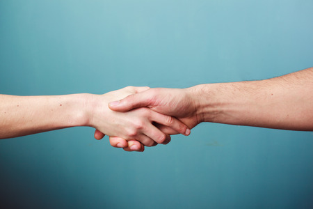 Young man and woman are shaking hands Stock Photo
