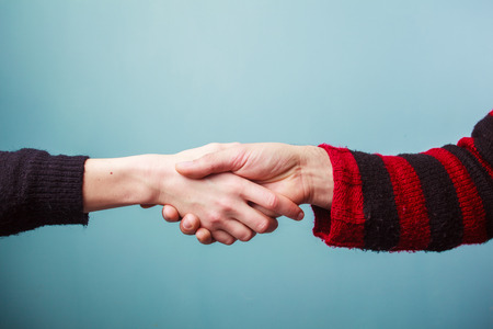 Young man and woman are shaking hands photo
