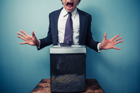shredder: Businessman has got his tie stuck in a paper shredder Stock Photo