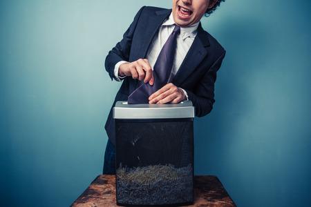 clumsy: Hombre de negocios torpe con su corbata atrapado en una trituradora de papel Foto de archivo