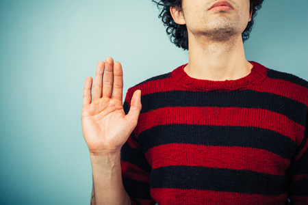 Young ethnic man is pledging allegience with his right hand raised photo