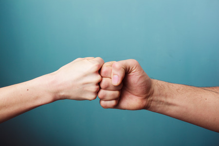 Young man and woman are fist bumping