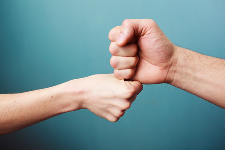 fist: Young man and woman are fist bumping