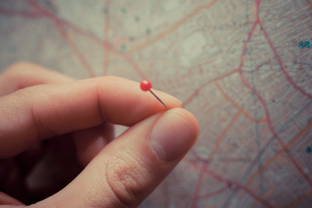 topographic map: Close up on a hand placing a pin on a map