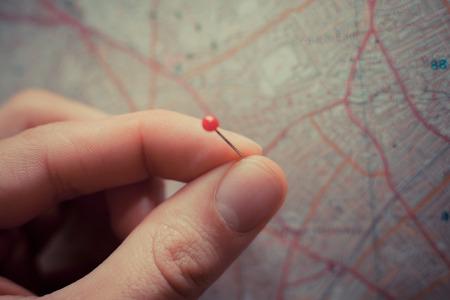 Close-up op een hand het plaatsen van een speld op een kaart Stockfoto