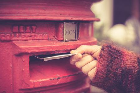 Close-up op de hand van een vrouw als ze is het posten van een brief