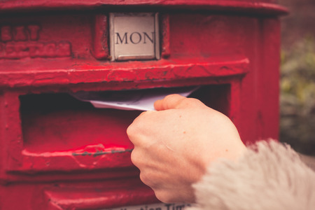 Closeup on a womans hand as she is posting a letter photo
