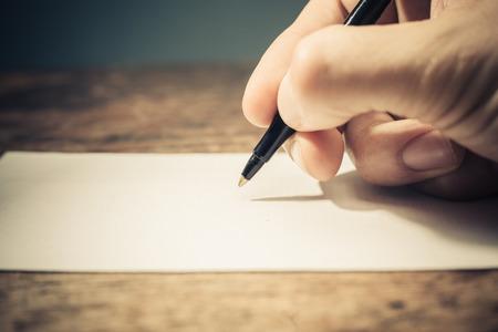 Primer en la mano la escritura de un hombre sobre un trozo de papel con un bolígrafo Foto de archivo