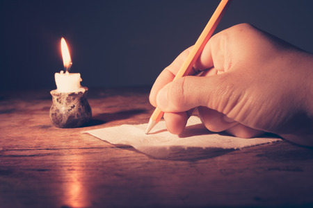 Closeup on a hand writing by candlelight