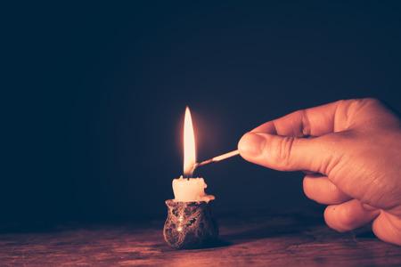 Man hand wordt het aansteken van een kaars
