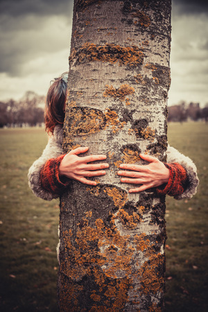 Young woman is in the park on a winters day and is hugging a tree