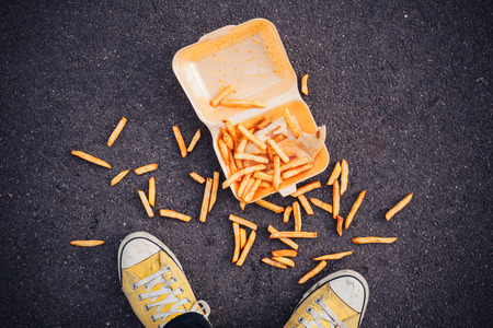 Young man has dropped his chips in the street Stock Photo