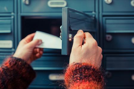 Closeup auf die Hand einer Frau, wie sie ist immer ihre Post aus ihrem Briefkasten Standard-Bild
