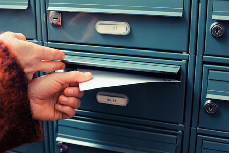 Closeup on afemale hand putting a letter in a letterbox