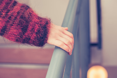 banister: Coseup on womans hand holding onto a banister Stock Photo