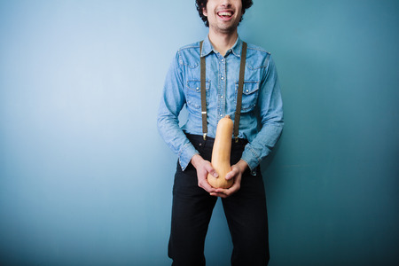 young farmer: Happy young farmer is showing off his big long butternut squash Stock Photo
