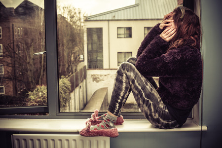 Sad young woman is sitting on the windowsill photo