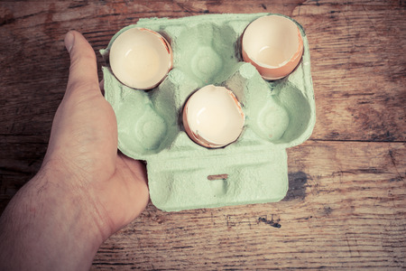 Hand holding a tray of egg shells at a table photo