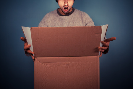 surprised face: Surprised young man is opening a large cardboard box with something exciting inside it Stock Photo