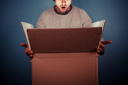 Surprised young man is opening a large cardboard box with something exciting inside it Stock Photo