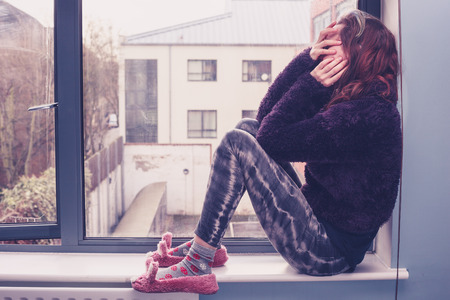 Sad young woman is sitting by the window photo