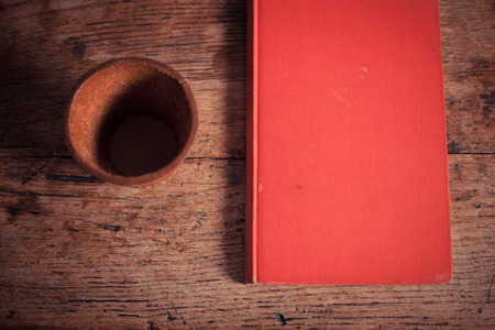 Leather dice shaker and a red book on a table photo