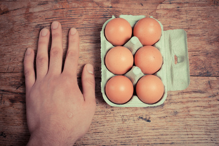 Six eggs in a cardboard tray on a wooden table with a hand next to them photo