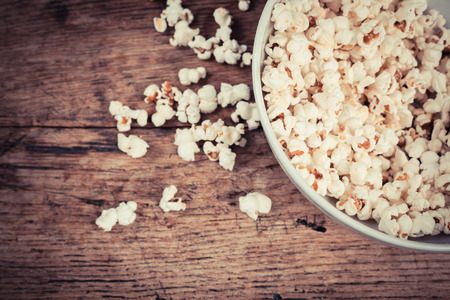A bowl of popcorn on a wooden table Stock Photo