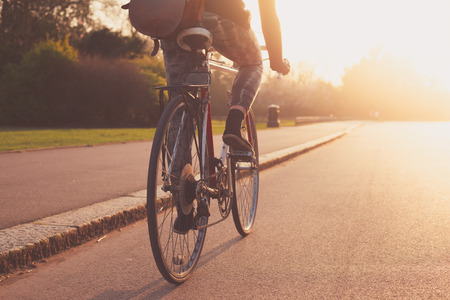 A young woman cycling into the sunset in the park photo