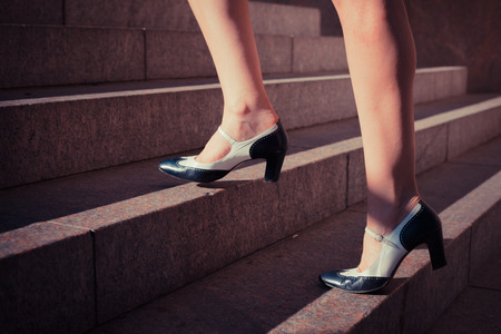 A young woman is walking up some stairs outside on a sunny day in the city photo