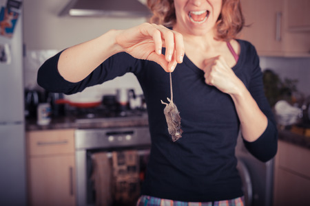 A disgusted young woman is holding a dead mouse by its tail in the kitchen