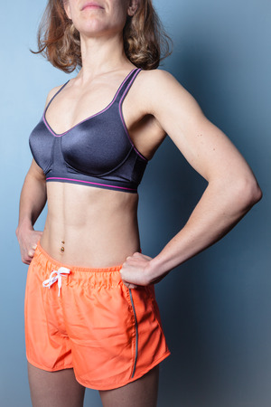 Fit young woman with toned abs standing in a dominant pose