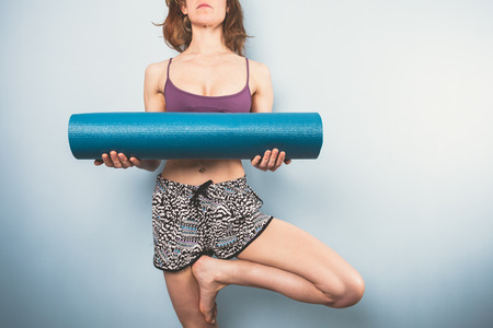 Athletic young woman in a tree pose is holding a yoga mat photo