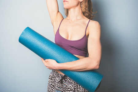 Athletic young woman is holding a yoga mat photo