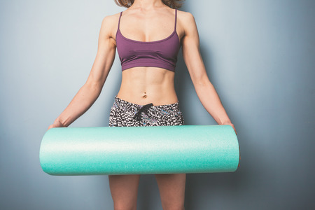 Athletic young woman is holding a foam roller for exercise