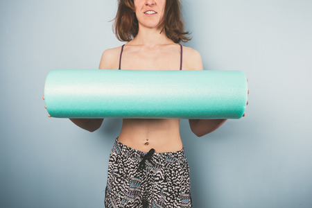 Athletic young woman is holding a foam roller for exercise photo