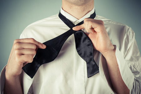 Young man is showing how to tie a formal bow tie